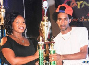 First Citizens Marketing Officer Nicole McDonald presents third place trophy to Ricky T in the Groovy Monarch competition.