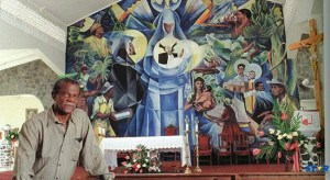 Standing tall with one of his greatest pieces - a mural at the Jacmel Church.