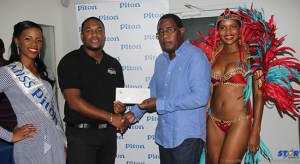 Piton Brand Manager Rohan Lovence presents cheque to Teddy Francis of the CPMA as Miss Piton Anya Edwin and a Carnival brand ambassador look on.