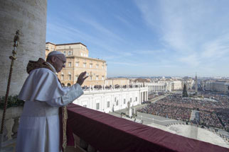 """Pope Francis waves during the """"Urbi et Orbi"""" (to the City and the World) Christmas message from the balcony overlooking St. Peter's Square at the Vatican on December 25, 2015. (Reuters/Osservatore Romano)"""
