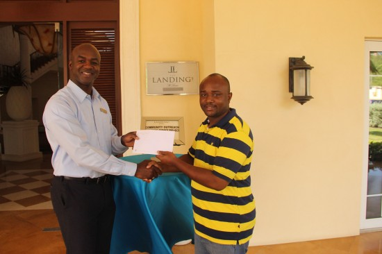 Landings GM Wilbert Mason (left) presents a cheque to Bannah Suffren for boys' grooming project.