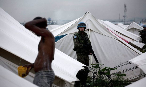 A UN soldier watches a man washing in a Haitian refugee camp. Sewage dispoal was so poor at UN military bases that it threatened to 'damage the reputation of the mission'. Photograph: Andres Martinez Casares/EPA