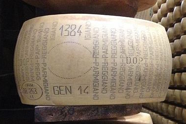 A wheel of Parmigian-Reggiano with identifiers indicating cheese house and production date. Image via Wikipedia.