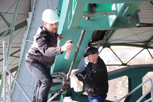 Elaskon-Manager Michael Kronschnabl (links) und Bergbahn-Gruppenleiter Carste Lauterbach von den DVB stehen auf der Gondel der Schwebebahn Dresden und schmieren das 39-Millimeter-Stahlseil. Foto: Heiko Weckbrodt