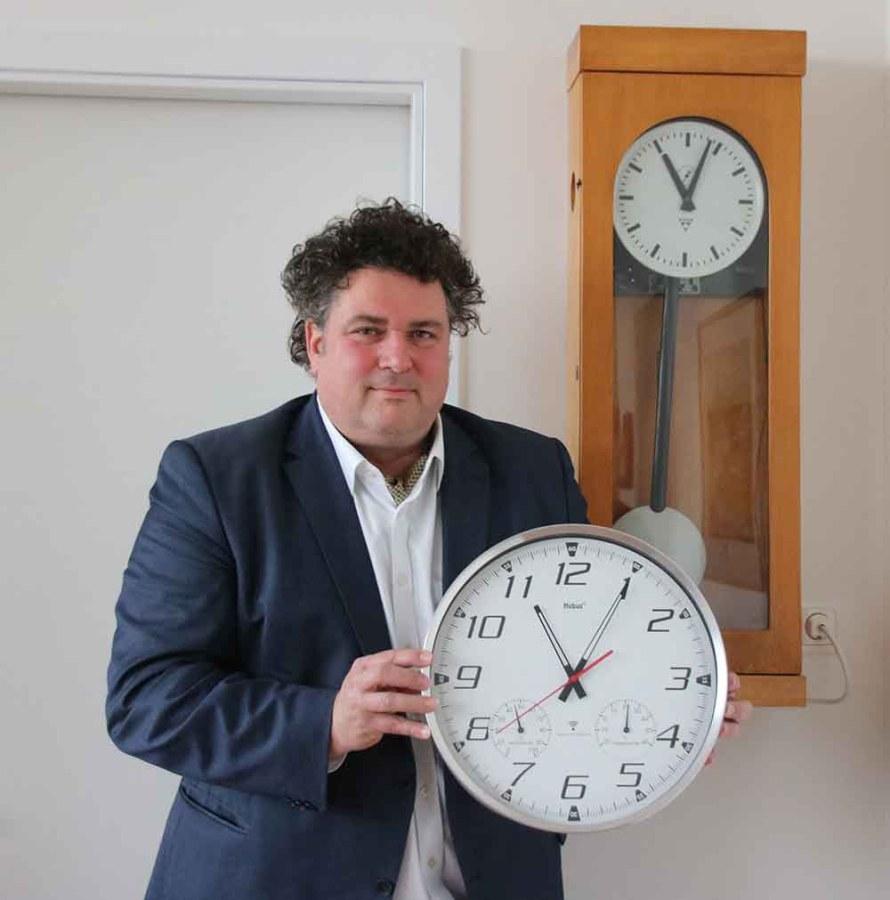 """Direktor Jürgen Küfner hat sich zum Semester-Thema """"Zeit"""" der Volkshochschule mit Uhren umgeben. Foto: Heiko Weckbrodt"""