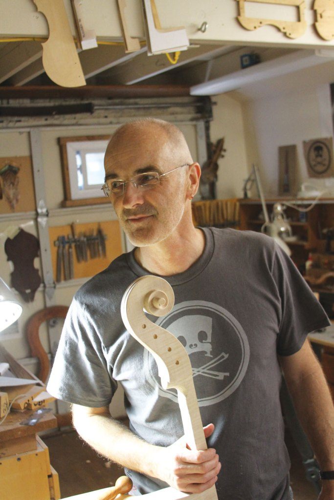 Luthier Andrew Carruthers, wearing one of his T-shirts with a hand-carved block design