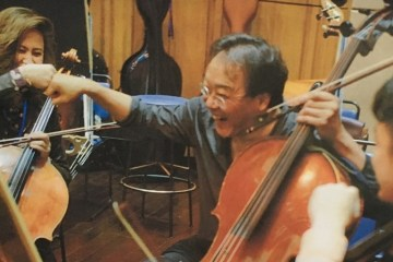 Yo-Yo Ma sits in the cello section with students during rehearsal at YMCG