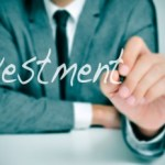 businessman sitting in a desk writing the word investment in the foreground