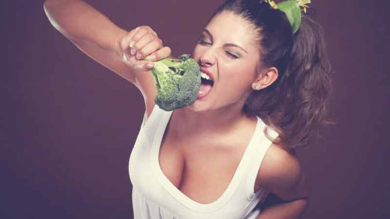 Girl-in-white-shirt-eating-broccoli