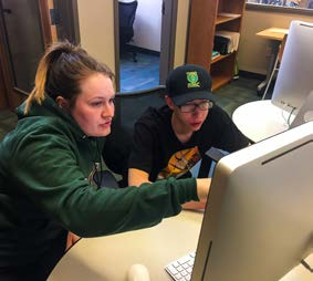 Writing Center tutor Madison Siebenaler assists Gideon Hudson. Photo by Roman Jones.