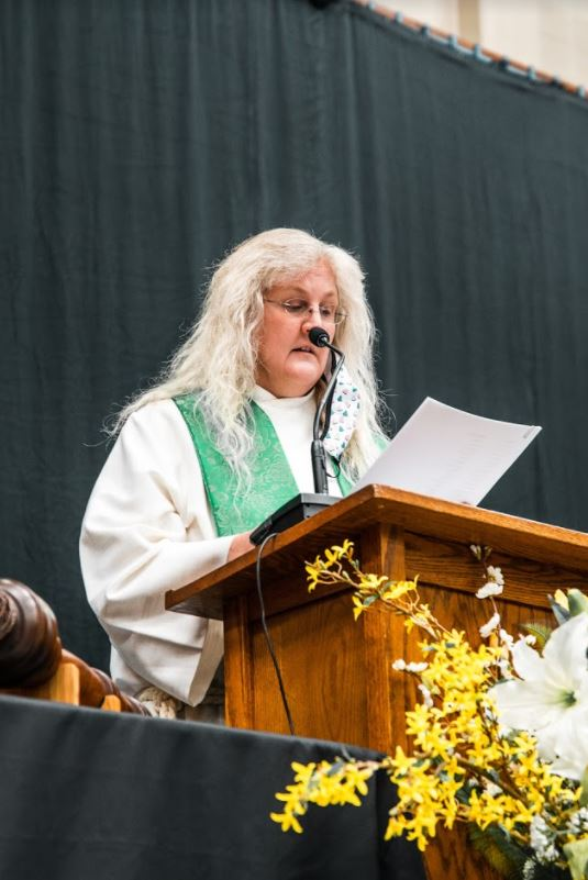 RMC's chaplain Kim Woeste giving a speech in the Fortin Gym during the graduation ceremony