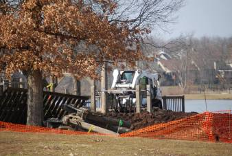 A Bobcat digs into the wooden playground equipment on Feb. 18