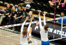 CSUN student (number 5) spikes the volleyball over the net away from two opponent blockers