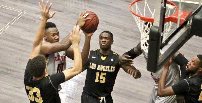 CSUN basketball player (number 10) fights through a group of Cal State LA players in hopes to score a point.