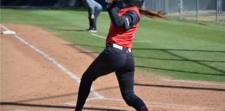 Student softball athlete bats at home base