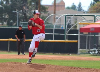 Student baseball athlete pitches during game