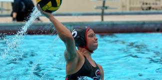 Water polo athlete throws ball as she lifts herself above water