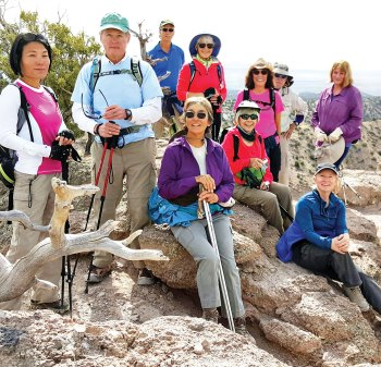 Hikers enjoying view atop tent rocks in New Mexico.