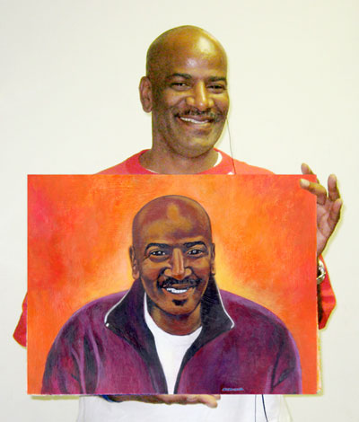 Hasan Abdullah holding the portrait painted by Deanna Yildiz