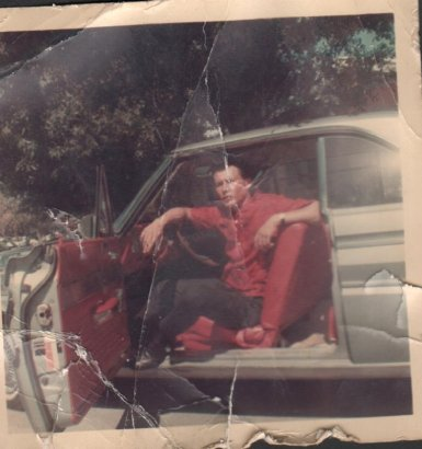 This is the original badly damaged photo of a man sitting in car that Deanna Yildiz had to repair.