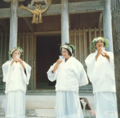 Priestesses in full garb ritually holding cups of sake