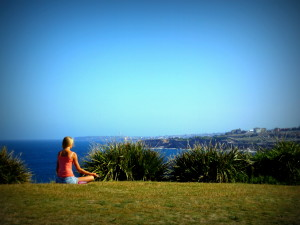 Young woman sitting cross-legged & meditating on grass on headland overlooking Sydney & Pacific Ocean