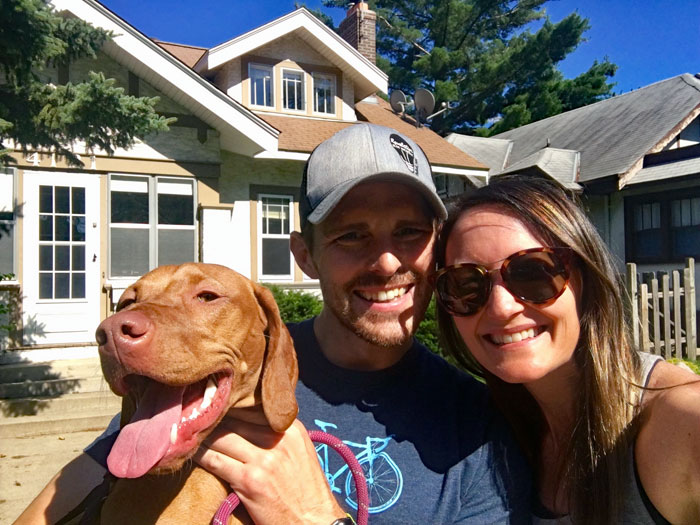 couple with vizsla in front of a bungalow