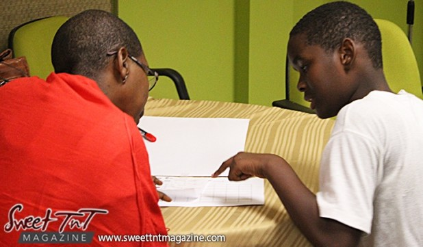 Boy and teacher at table at Launch Rockit in sweet t&t for Sweet TnT Magazine in Trinidad and Tobago