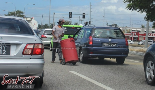 Juice and water vendor on the streets in between vehicles at red traffic light on highway in sweet T&T for Sweet TnT Magazine, Culturama Publishing Company, for news in Trinidad, in Port of Spain, Trinidad and Tobago, with positive how to photography.