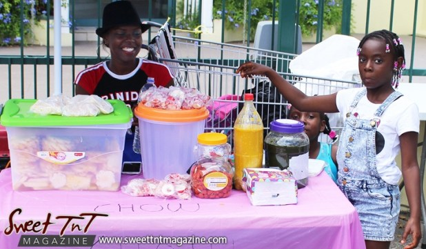 Young vendors sell pineapple chow and sweet and salt prunes on Ariapita Avenue, Carnival 2017 in sweet T&T for Sweet TnT Magazine, Culturama Publishing Company, for news in Trinidad, in Port of Spain, Trinidad and Tobago, with positive how to photography.