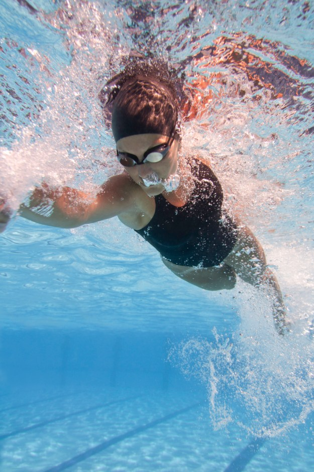 Front crawl swimmer speeding through the pool