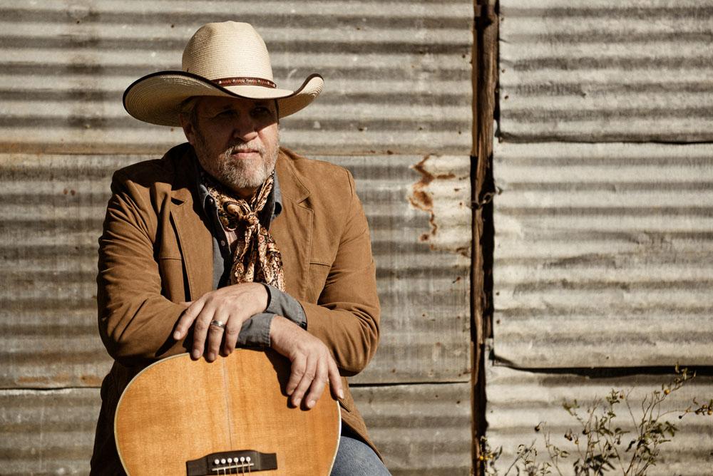 S.W. LaFollett leaning on a guitar in Austin, TX