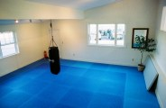 The lower dojang is for warming up and small-group instruction. It features a heavy bag and stretching equipment.