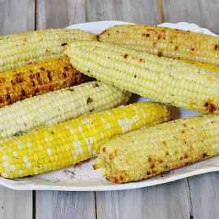 Herb and Parmesan Grilled Corn.. Fresh shucked corn is slathered with a compound butter containing fresh herbs, Parmesan cheese and a seasoning blend, wrapped in foil and grilled