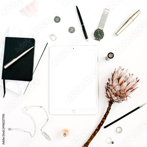 blogger or freelancer workspace with blank screen tablet protea flower notebook watches and feminine office accessories