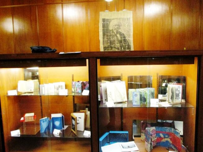 "(bottom shelf, far left) ""The Accordion Book of Short Stories;"" (on wall)"