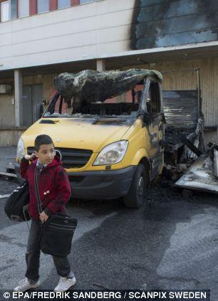 Un ragazzo cammina a scuola passato un camion bruciato all'esterno di un edificio bruciato