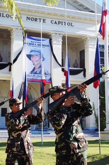 GUN SALUTE FOR A FALLEN HERO. Two soldiers fire their gun into the air as their salute to fallen comrade PO2 Omar Nacionales during the mass and wreath laying ceremony held in front of the provincial capitol last Jan. 29, 2015. (PGIN/CMO)