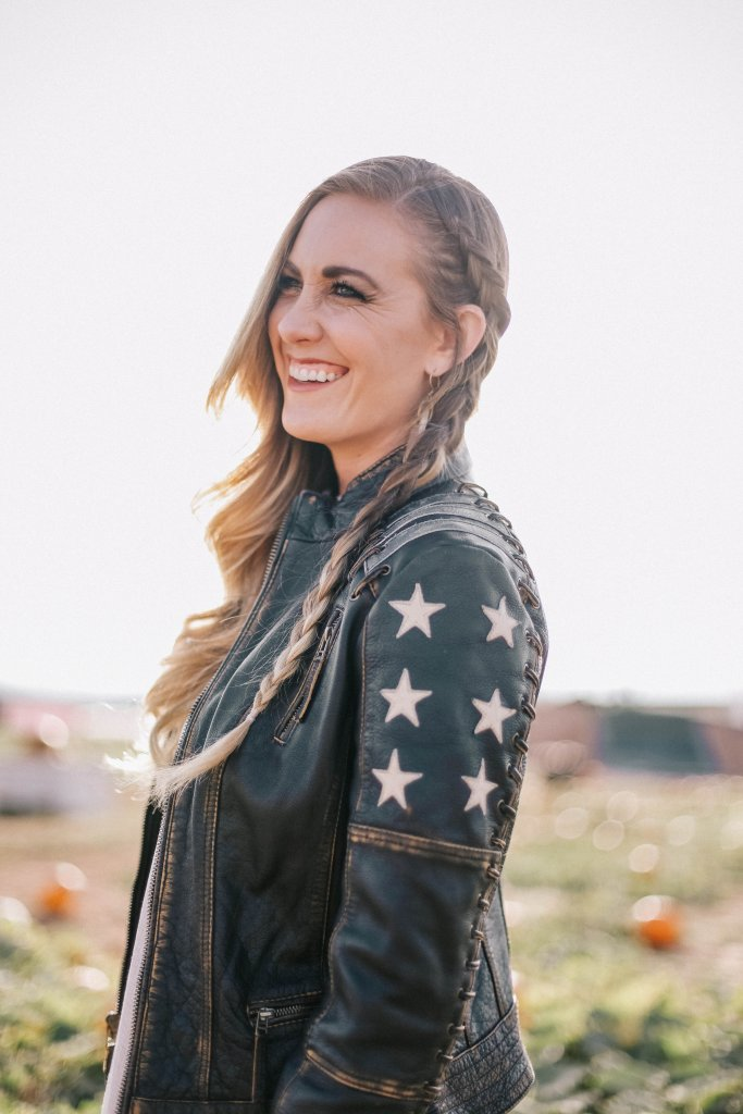 picture of blogger, Tazia Lynne, wearing the BLACK RIVET DISTRESSED STARS AND STRIPES LEATHER JACKET W/ LACING DETAIL.