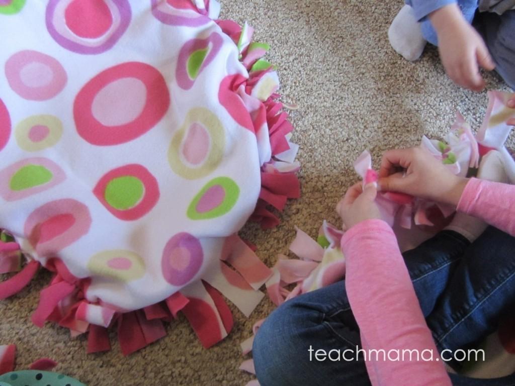 girl tying fleece blanket together