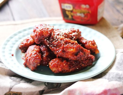 Crispy fried chicken is covered in a korean chilli paste glaze and garnished with sesame seeds