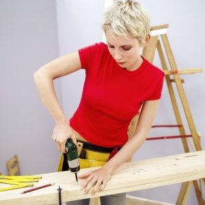 Woman Boring a Hole in a Wooden Board with a Drill