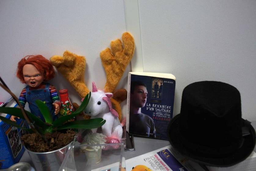 Various toys, tchotchkes, souvenirs, and a French book about Facebook founder Mark Zuckerberg are seen inside the offices of Facebook in Paris, France on Nov. 29, 2010.