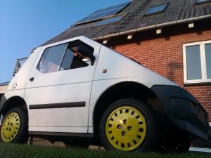 nutidens hus med solceller og elbil i haven