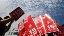 Demonstrators prepare signs supporting the raising of the federal minimum wage during May Day demonstrations in New York May 1, 2014. REUTERS/Lucas Jackson