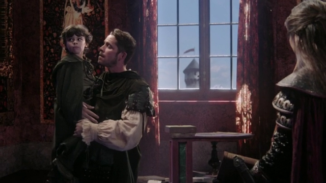 a screencap of robin hood (play be sean maguire) holding his son, roland (played by raphael alejandro)