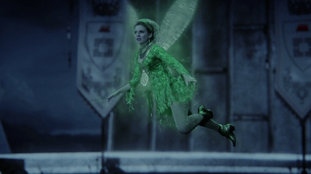 a screencap of tinke bell (played by rose mciver) flying surrounded by green pixie dust