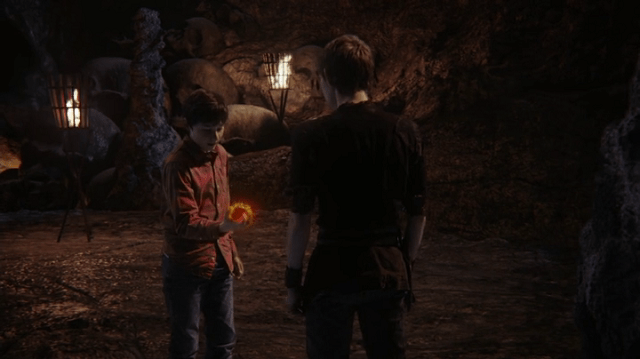 a screencap of henry (played  by jared s. gilmore) taking his heart out while peter pan (played by robbie kay) looks on