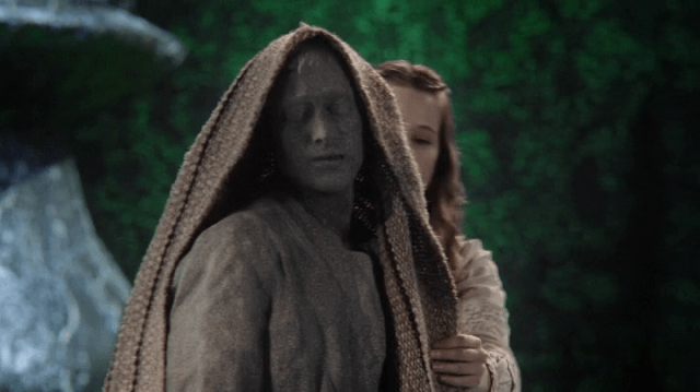 a screencap of alice (played by sophie lowe) covering the stone knave with a blanket