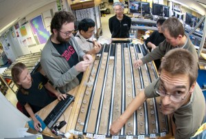 Researchers hailing from all corners of the globe work together to take small samples from the Louisville Seamount Trail cores. These samples will be analyzed to determine the age, composition, and physical properties of the rocks. (Credit IODP-USIO)